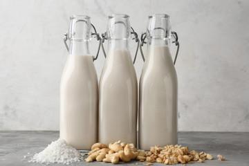 Fotobehang - Assortment of tasty vegan milk on grey table