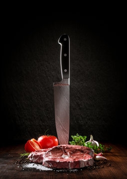 Beef rare steak on a wood desk with chef knife. Around are fresh tomatoes, sweet and spicy peppers, greens and spices, white salt and black pepper.