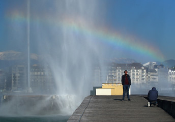 People take pictures with a rainbow created by the water falling from the Jet d'Eau water fountain in Geneva