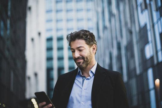 Businessman walking in city using smartphone