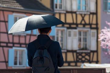 asian tourist with umbrella  taking a picture on bridge