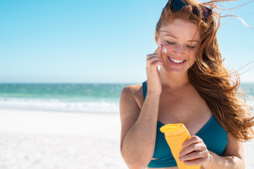 Woman with freckles applying sunscreen on face