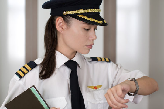 Professional female pilot checking the time at the airport.