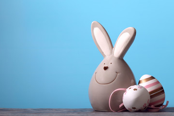 On a wooden beige surface, an Easter bunny and two with drawings of white eggs on a blue background. Cut off picture, horizontal, free space for text, side view. Easter concept.