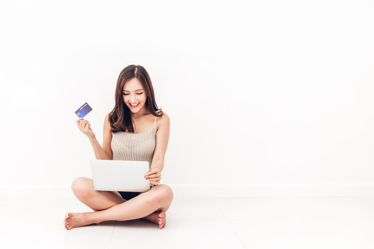 Beautiful woman shopping online with technology of laptop computer and credit card sitting on the floor against copy space for adding text with white wall background