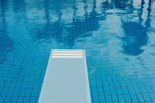 Swimming pool with refreshing blue water, springboard and reflection