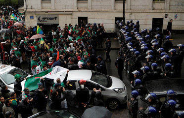 Police officers stand guard as people take part in a protest calling on President Abdelaziz Bouteflika to quit