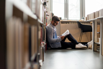 Young student in library reading a book