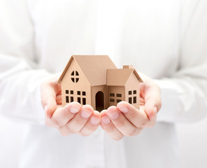 Property insurance. Cardboard house miniature in hands