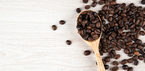Wall Mural - wooden spoon and roasted coffee beans close up