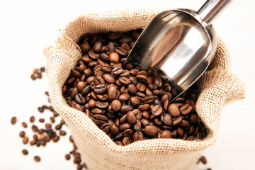 Wall Mural - metal scoop in the bag with roasted coffee beans close up