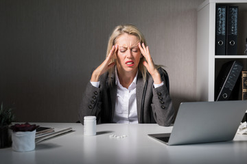 Woman feeling headache at work