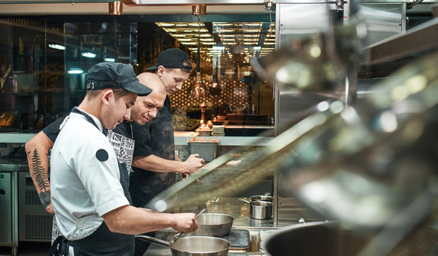 Culinary school. Strict young chef in apron looking carefully how his assistant cooking at restaurant kitchen