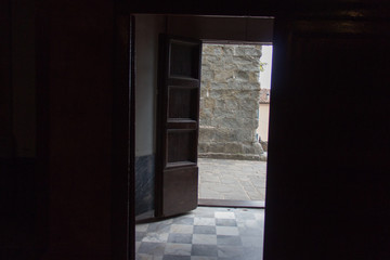Exit door at the end of a dark ancient room.