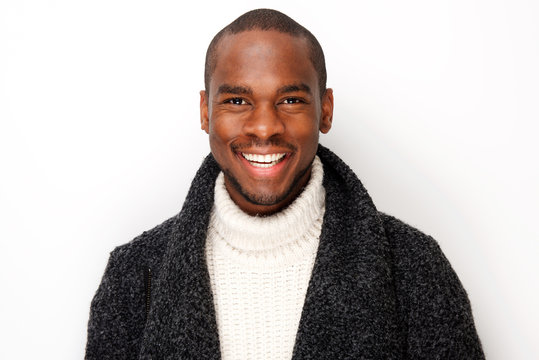 Close up smiling young black man with coat by isolated white background