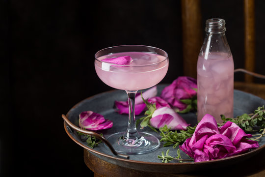 Summer refreshment drinks. Light pink rose cocktail, with rose wine on dark background. With rose flowers. Copy space