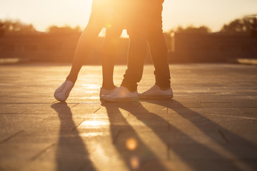 Legs of man and woman. Loving couple embracing at sunset