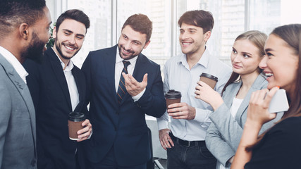 Fototapete - Happy colleagues talking, having coffee break in office