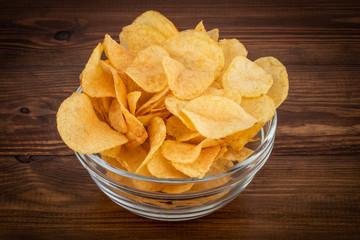 Crispy potato chips in bowl on wooden background