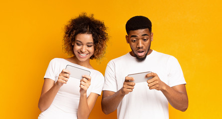 Emotional african-american man and woman watching videos online