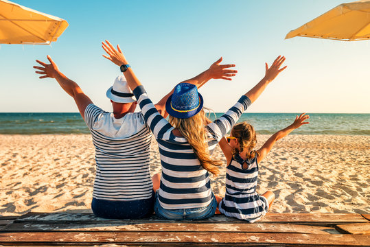 family in striped clothes on the beach