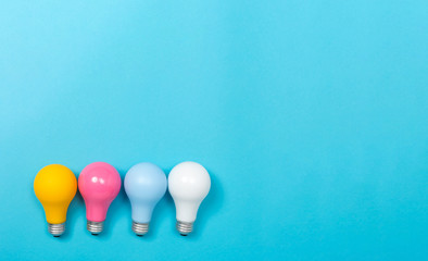Wall Mural - Colored light bulbs on a blue paper background