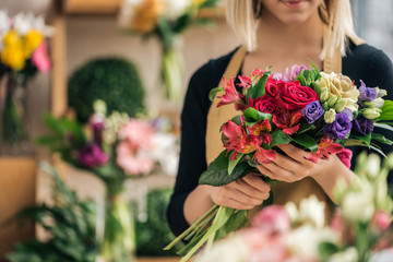 Obraz Cropped view of florist in apron holding bouquet in flower shop - fototapety do salonu