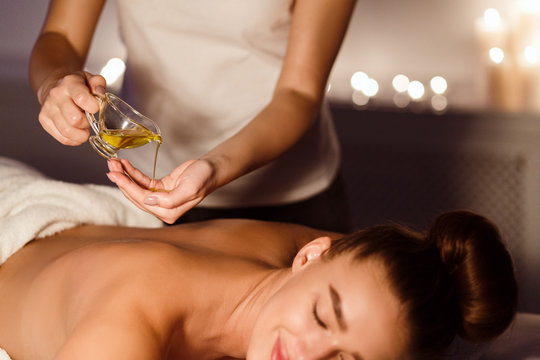 Masseur pouring aroma oil on hand, preparing for massage