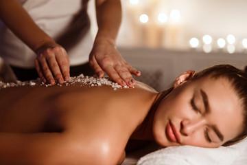 Woman getting salt scrub treatment in the spa