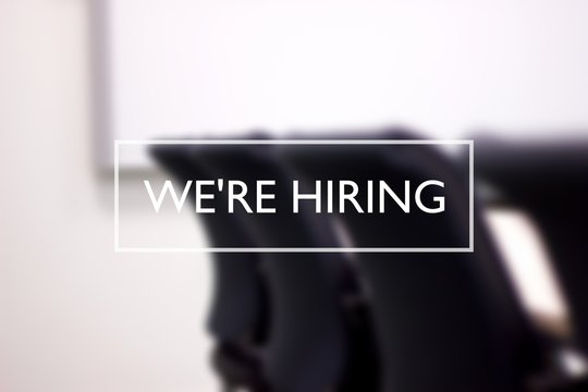 We're hiring text against blurred meeting room. Recruitment, employment concept