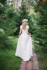 the bride is on the path in the woods