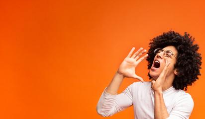Emotional black guy screaming on orange panorama background