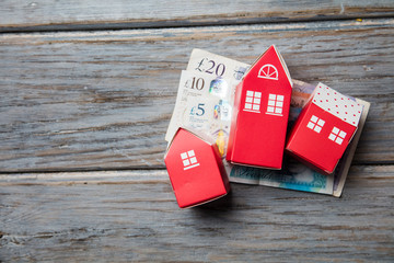 Housing cost. Paper toy house with British currency notes