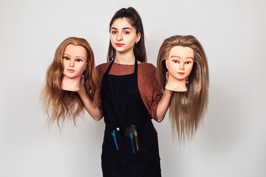 young girl hairdresser holds in hands two mannequin heads.