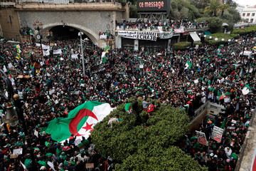 People carry banners and Algerian national flags during a protest calling on President Abdelaziz Bouteflika to quit, in Algiers