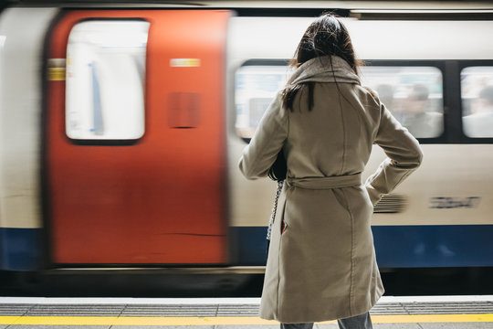 Rear view of a woman standing on a London Underground station platform, moving train on the background.