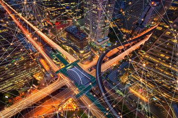 Digital network connection lines of Sathorn intersection, Bangkok Downtown, Thailand. Financial district and business centers in smart urban city in Asia. Skyscraper and high-rise buildings at night.