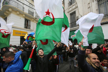 People wave Algerian national flags during a protest calling on President Abdelaziz Bouteflika to quit, in Algiers