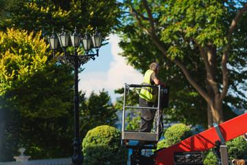Street worker on the lifting machine. Garden work in the Park. Alley with green trees.