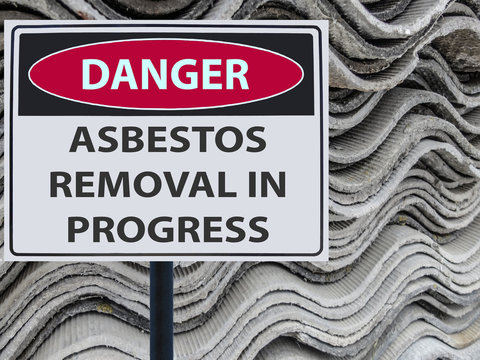 sign danger asbestos removal in progress and a stack of sheets roof of asbestos.