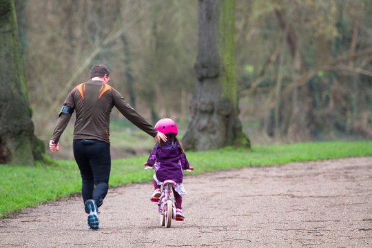 A father runs alongside his daughter who is learning to ride a bike in Shrewsbury, Shropshire, England.