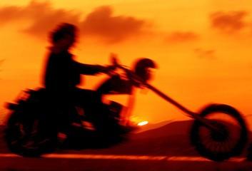 BIKER RIDES PAST THE SUNSET IN IGUMENITSA.