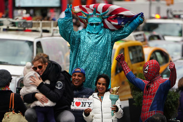 A person dressed as the Statue of Liberty poses for photos for money in Times Square in New York