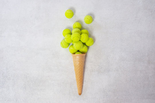 Ice cream cone with tennis ball on white background. Minimal food concept