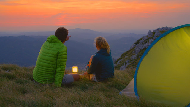 CLOSE UP: Man showing the landscape to girlfriend while sitting by their tent.