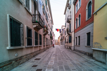 narrow Venetian street surrounded by colourful building