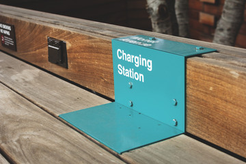 An outdoor charging station on a wooden table structure