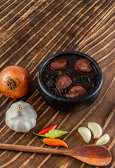 close-up of dark clay pot with black kidney beans with calabrian sausage, wooden background