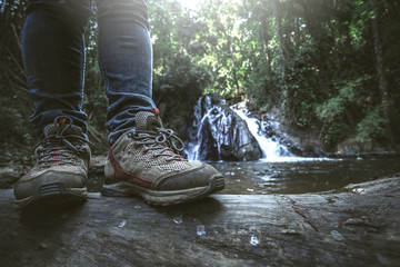 Close up shoes of traveler man standing in front waterfall. hiking concept. Fototapete