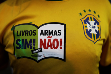 """A protester wears a T-shirt with the colours of the Brazilian national soccer team with a sign reading """"Books Yes, Weapons No"""" during a protest against Brazil President Jair Bolsonaro's proposed pension reform project in Sao Paulo"""
